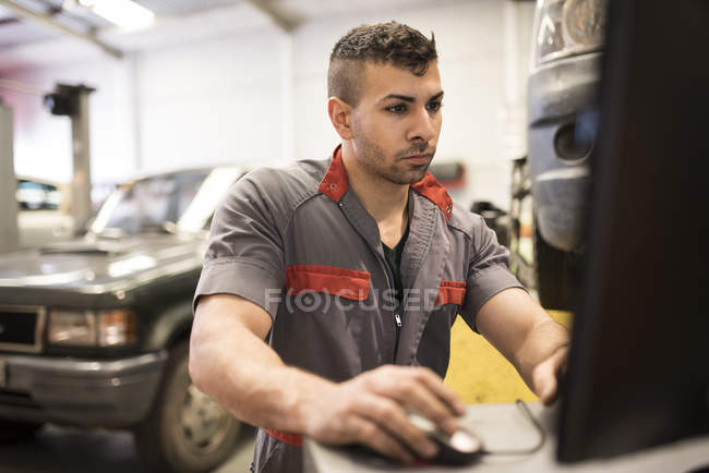 Fokussierte Mechaniker Werkstatt Computer mit — Stockfoto