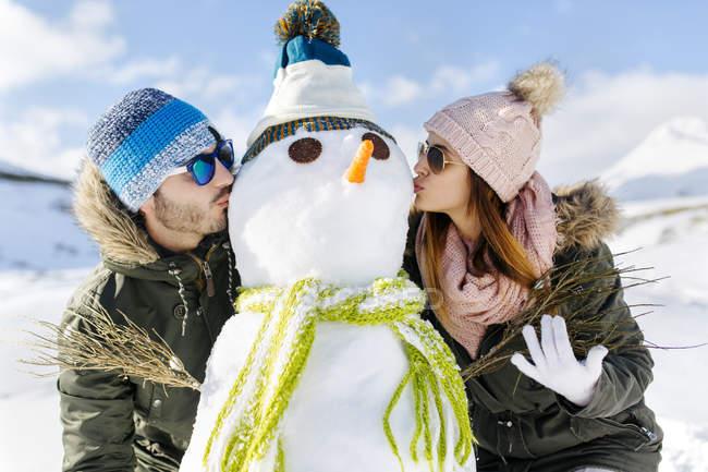 Spain, Asturias, couple kissing a snowman — Stock Photo