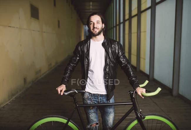 Joven sonriente con bicicleta fija - foto de stock