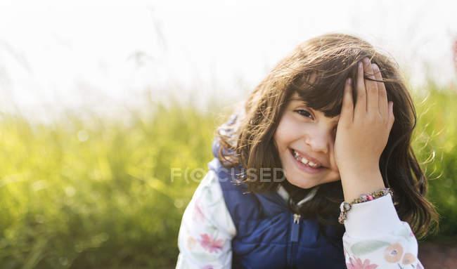 Retrato de sorridente menina cobrindo o olho com a mão — Fotografia de Stock