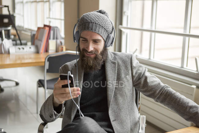 Young businessman wearing beanie hat using smartphone — Stock Photo