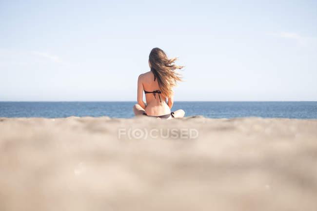 Молодая женщина расслабляющий на пляже, вид сзади — стоковое фото