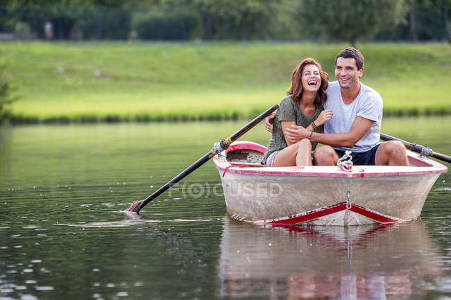 Young couple having fun in a rowing boat on lake — Stock Photo