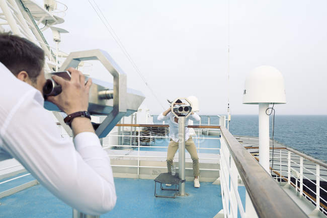 Two young men watching each other through telescopes on ship — Stock Photo