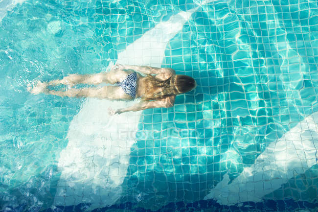 Back view of woman diving in a swimming pool — Stock Photo
