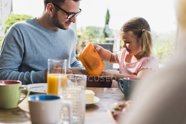 Daughter packing lunch box in father bag — Stock Photo
