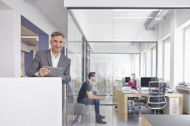 Uomo d'affari maturo in ufficio moderno utilizza la compressa di digital — Foto stock