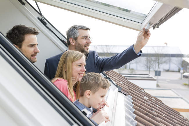 Family and estate agent looking through rooflight — Stock Photo