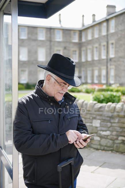 Großbritannien, Bristol, senior woman mit Smartphone während der Wartezeit an Bushaltestelle — Stockfoto