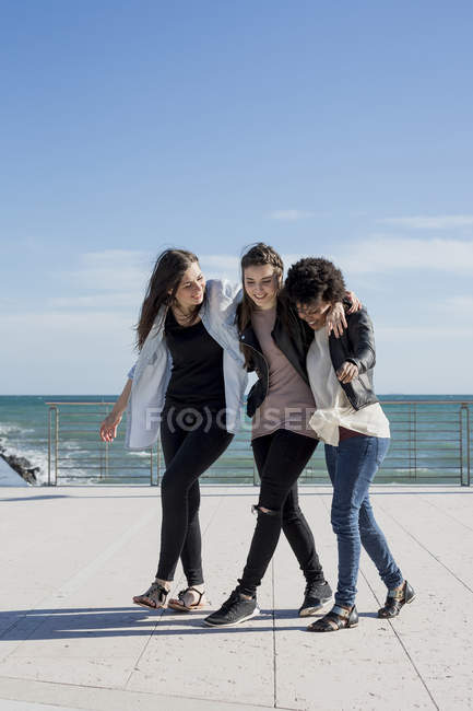 Three young women walking arm in arm by the sea — Stock Photo