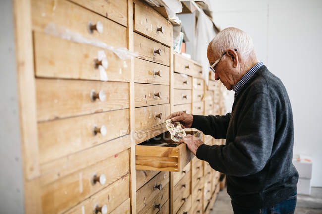 Senior man looking for decals for ceramics — Stock Photo