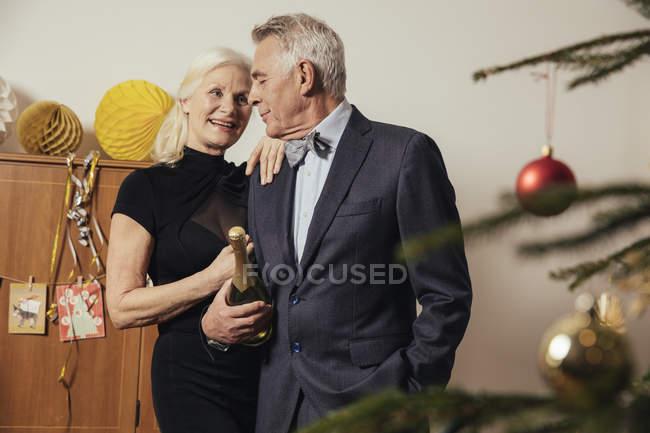 Пожилые супружеские пары Холдинг бутылка шампанского в канун новой Йера — стоковое фото
