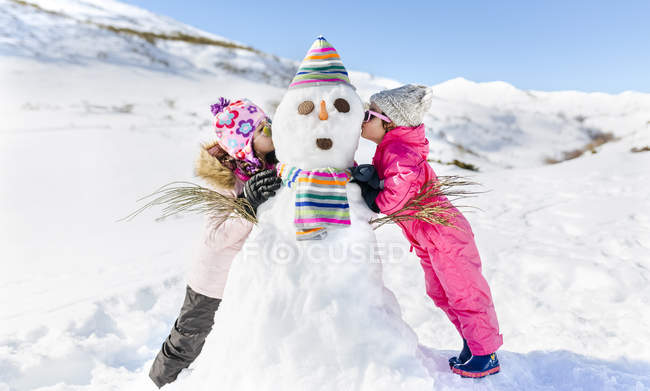 Bambini svegli che giocano con pupazzi di neve, baciare — Foto stock