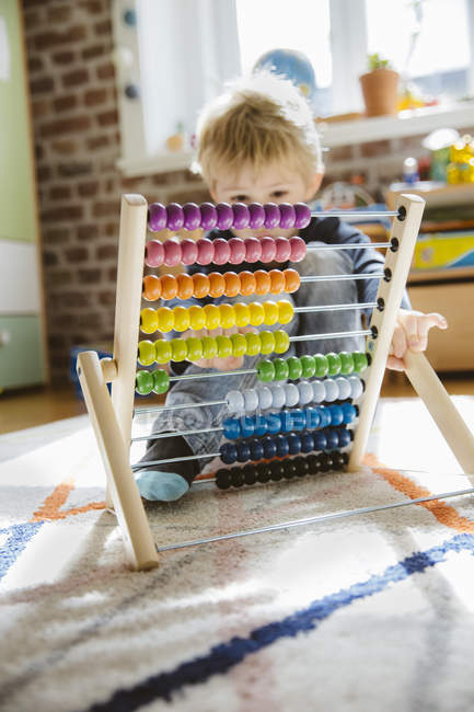Little boy playing with abacus in children room — Stock Photo