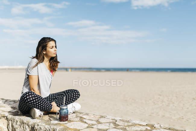 Молода жінка з здоровий напій, сидячи на стіні на пляжі — стокове фото