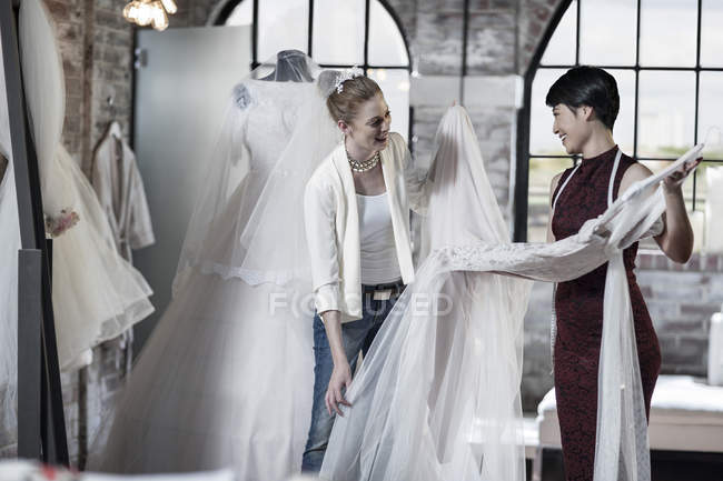 Wedding dress designer and bride standing in bridal store — Stock Photo