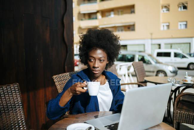 Молодая женщина с ноутбуком сидит в уличном кафе и пьет кофе — стоковое фото