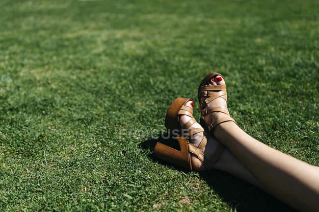 Füße von Frau entspannend auf grünen Rasen — Stockfoto