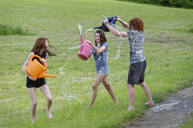Three teenagers with watering cans splashing with water — Stock Photo