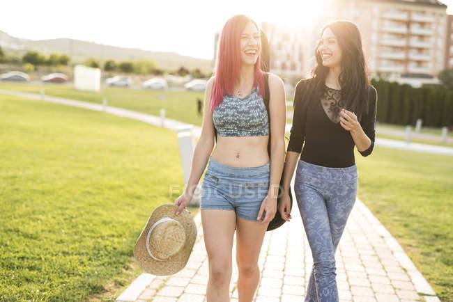 Two girl friends walking in park, having fun — Stock Photo