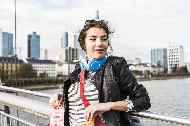 Jovem da cidade com sacolas de compras e croissant — Fotografia de Stock