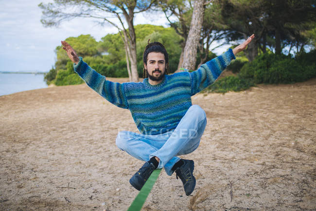 Young man with dreadlocks practicing on a slackline — Stock Photo