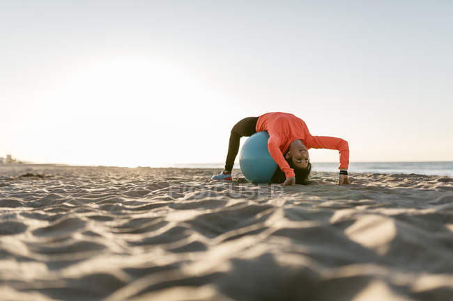 Woman doing sports with gym ball early in the morning on the beach — Stock Photo
