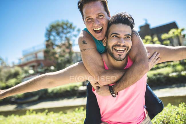 Смеющийся мужчина, несущий своего парня на спине — стоковое фото
