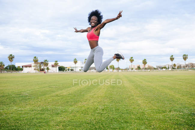 Laughing black athlete jumping for joy — Stock Photo