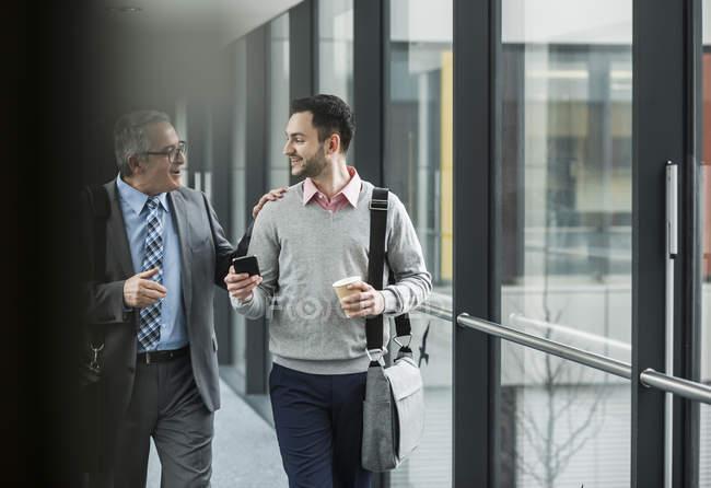 Due uomini d'affari che camminano e parlano sul pavimento dell'ufficio — Foto stock