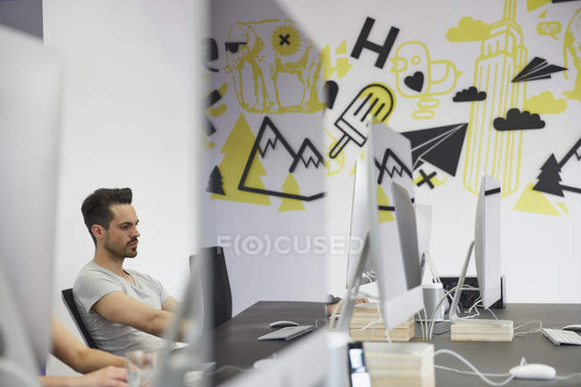 Caucasian businessman working at creative office — Stock Photo