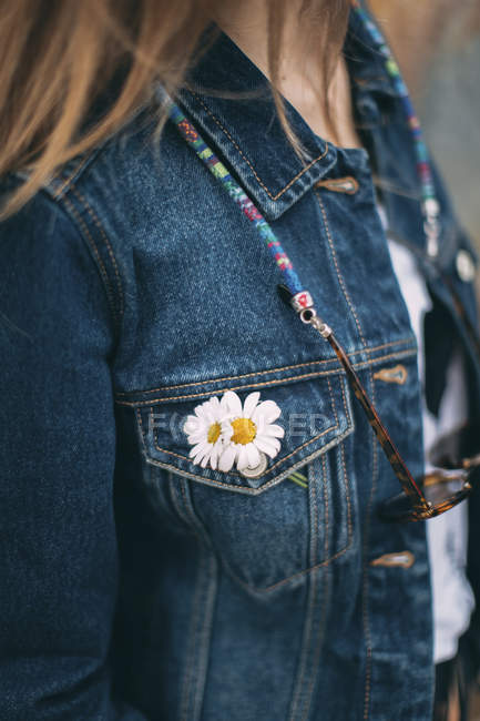 Daisies at pocket of woman's denim jacket — Stock Photo