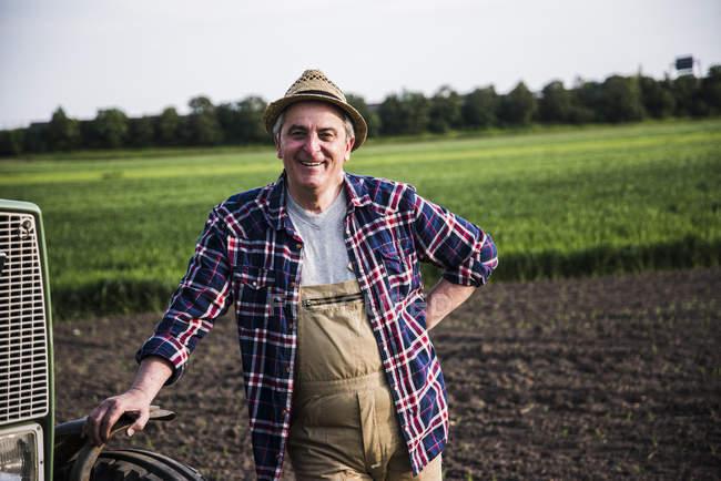 Porträt eines lächelnden Bauern vor einem Feld — Stockfoto