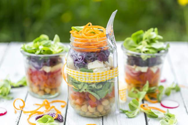 Радуга салат с нута, помидоры, морковь, красная капуста, красный редис, салат и сыр фета сыр в очках — стоковое фото