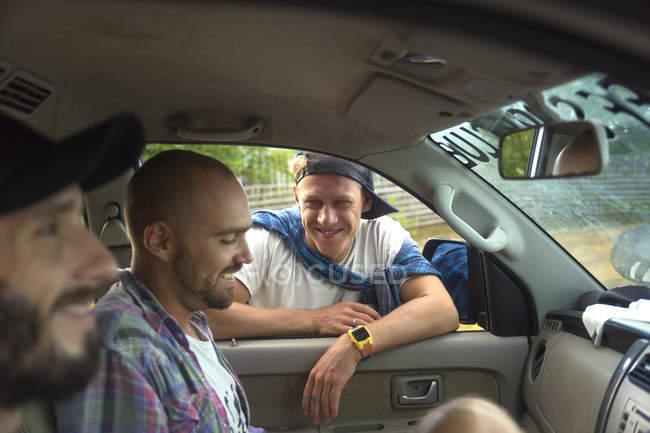 Улыбающиеся молодые люди, выступая в автомобиле — стоковое фото