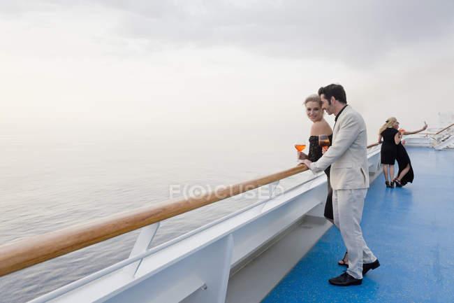 Vier Personen mit Aperitif an Deck eines Kreuzfahrtschiffes — Stockfoto