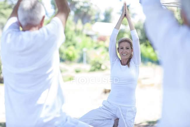 Pareja mayor practicando yoga junto con instructor - foto de stock