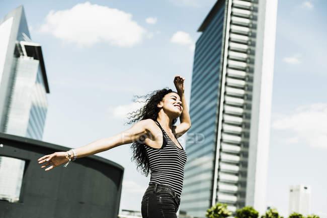 Begeisterte junge Frau mit ausgestreckten Armen im freien — Stockfoto