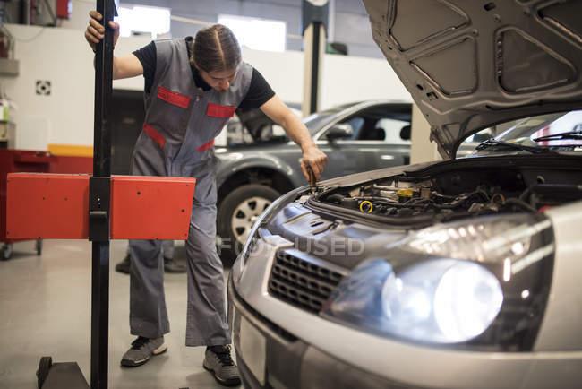 Mechanic adjusting and testing of car lights in workshop — Stock Photo