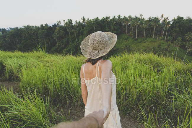 Back view of woman in nature holding hand of her boyfriend — Stock Photo