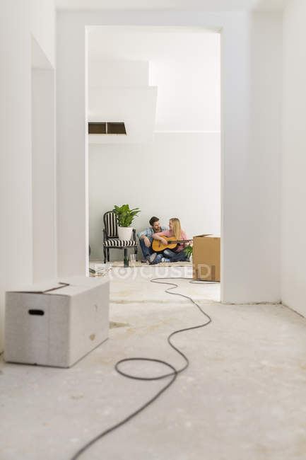 Couple with guitar relaxing on the floor of their unfinished new home — Stock Photo