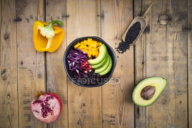 Lunchschale mit schwarzem Reis, Avocado, gelber Paprika, Rotkohl und Granatapfelkernen auf Holz — Stockfoto