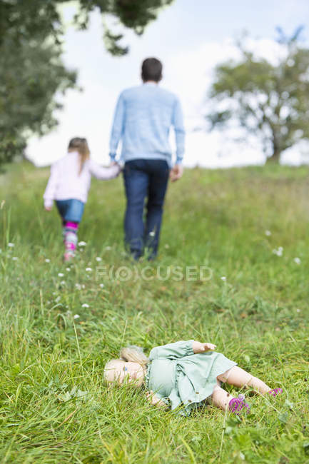 Doll lying on meadow while man going away with little girl — Stock Photo