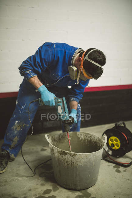 Bricklayer mixing cement in bucket — Stock Photo