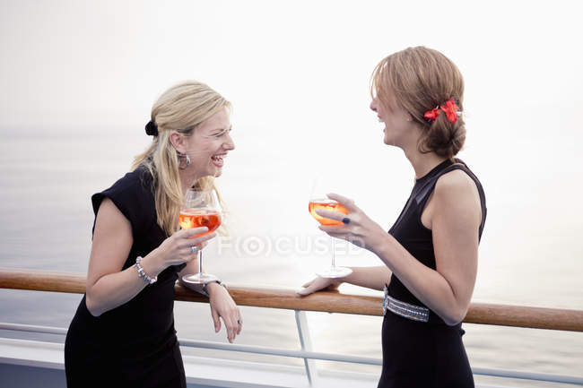Two laughing women with aperitive  stending on deck of a cruise liner — Stock Photo