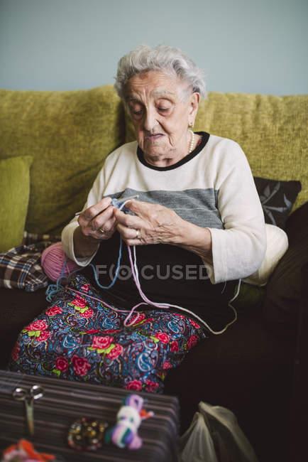 Portrait de crochet femme âgée assise sur le canapé à la maison — Photo de stock