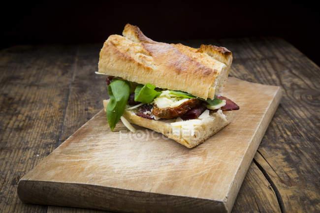 Сендвіч, французький білий хліб, підкопчену шинку, базилік, сушені помідори і сиром Пармезан — стокове фото