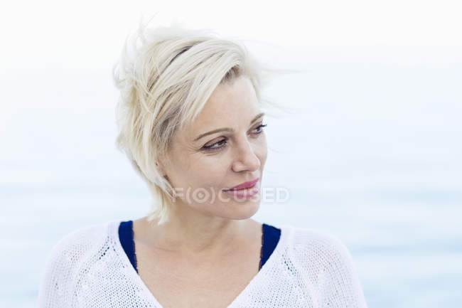 Portrait of blond woman in front of the sea — Stock Photo