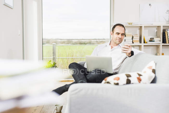 Businessman using laptop and cell phone on couch — Stock Photo