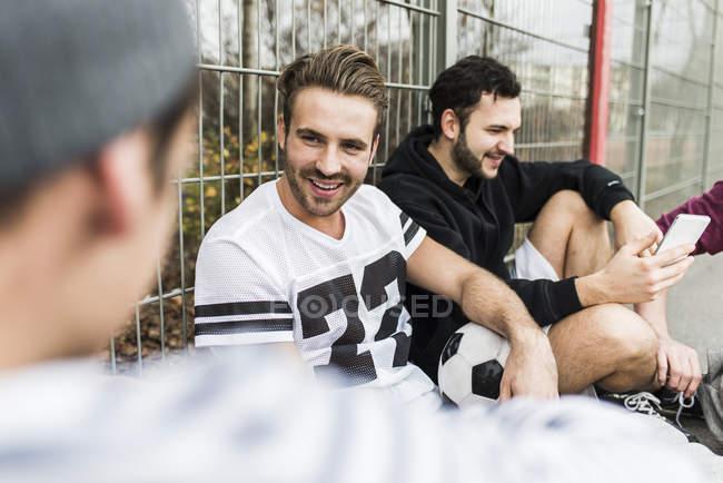 Jóvenes futbolistas relajándose juntos al aire libre - foto de stock